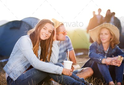 Teenagers sitting on the ground in front of tents, resting