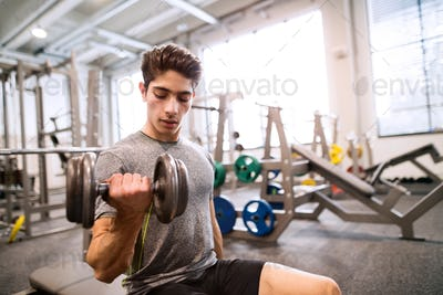 Hispanic man in gym sitting on bench, working out with weights