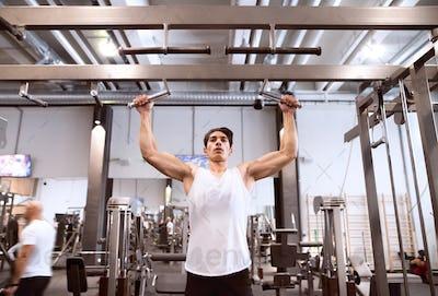 Hispanic man in gym doing pull-ups on horizontal bar