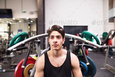 Hispanic man in gym prepared for training on fitness machine.
