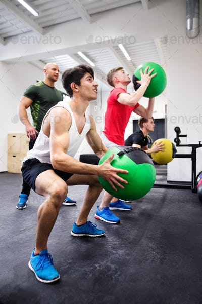 Men in gym with trainer exercising with medicine balls.