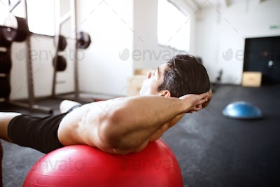 Fit hispanic man in gym training, working abs, doing crunches