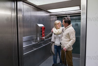 Beautiful senior couple with luggage standing in modern elevator.