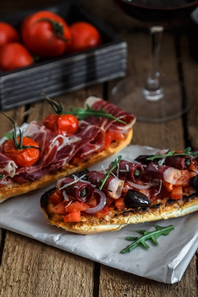 Tapas on crusty bread with red wine