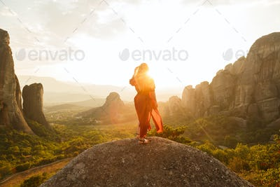 Young woman in red dress looking at majestic sunset in Meteora valley, Greece