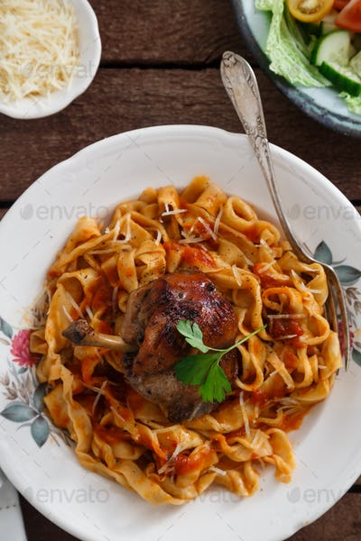 Italian homemade pasta, pappardelle with tomato sauce and braised rabbit, top view close-up