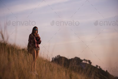 Young stylish hipster girl enjoy sunset on viewpoint. Travel woman with backpack