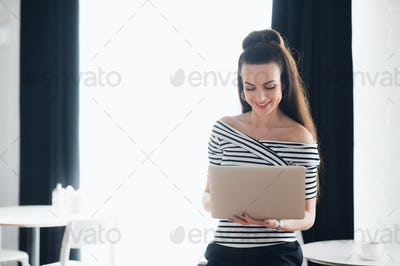 Young attractive brunette woman holding a laptop and typing, while looking at the screen. Adult