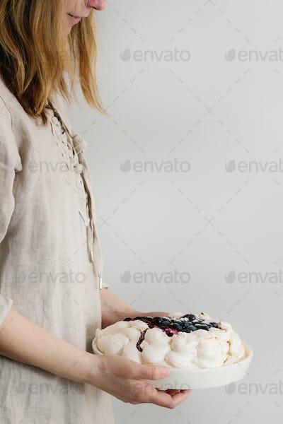 Meringue cake Pavlova in female hands