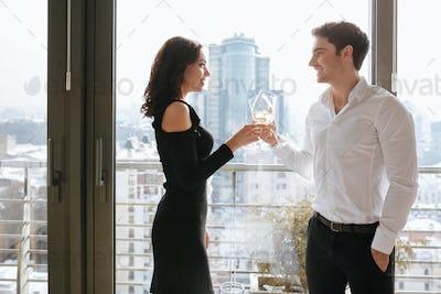 Happy loving couple standing near window drinking alcohol