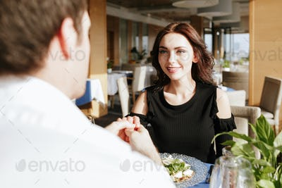 Smiling loving couple sitting in restaurant indoors