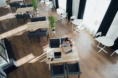 Overhead shot of a female using her laptop in a sidewalk cafe. Top view of an adult woman sitting at