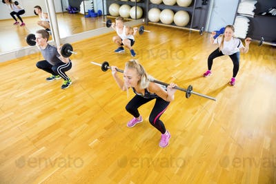 Friends in Group Lifting Barbell Rods In Fitness Gym