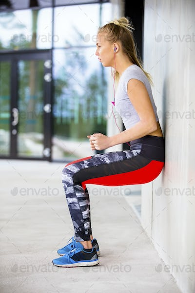Side View Of Sporty Young Woman Exercising Against Wall