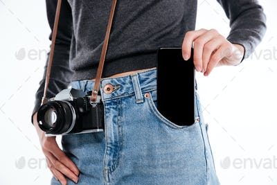 Portrait of a woman in denim jeans with retro camera