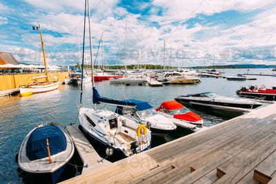 Norway, Oslo, Aker Brygge District. Wooden Sea Pier With Moored