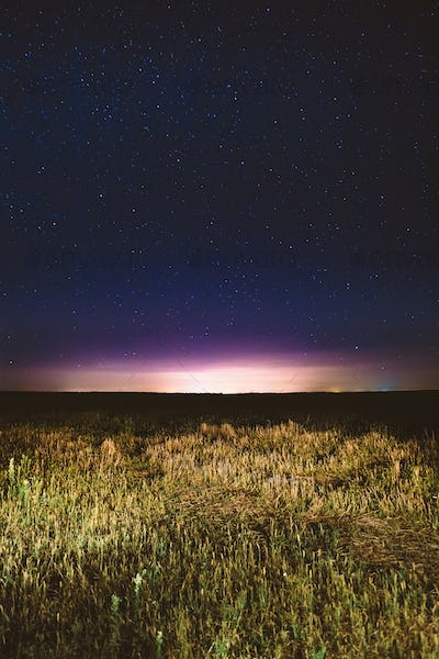 Night Starry Sky Above Field And Yellow City Lights On Backgroun