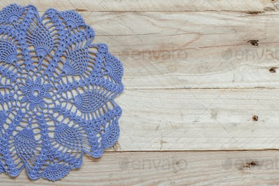 Blue crochet doily on the old wooden table