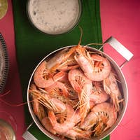 Shrimp on a pink table, glass with white wine and sauce