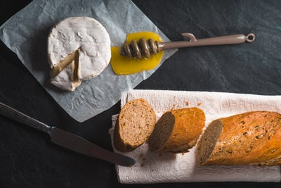 Brie cheese, pieces of baguette, honey on parchment