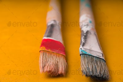 Two paint brushes on a yellow table
