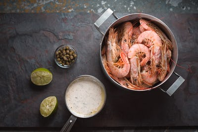 Shrimp in a saucepan, sauce, capers and on a slate free space