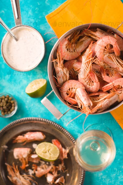 Shrimps in a saucepan on a yellow napkin, sauce, plate