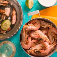 Casserole with shrimps, capers, lime, sauce on the table