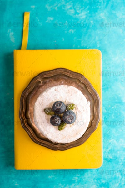 Cake with blueberry on a yellow notebook free space