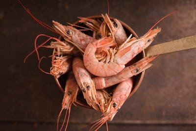 Large shrimps in a saucepan on a metallic background