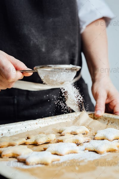 Person covering cookies with powdered sugar