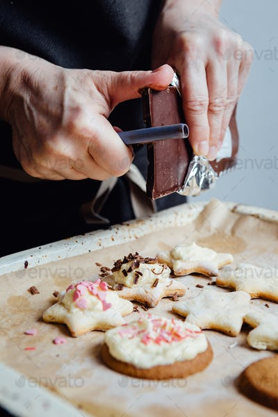 Cook decorating cookies with chocolate