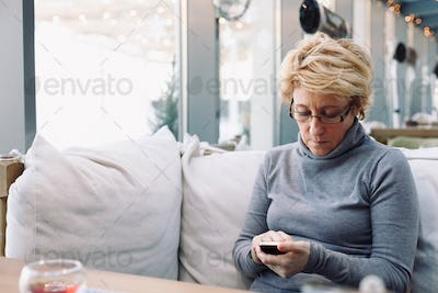 Mid age woman with cell phone sitting cafe