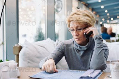 Mid age woman talking on cell phone sitting cafe