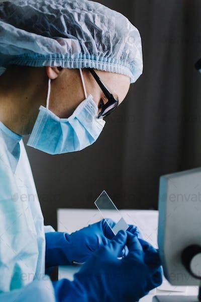 Female scientist arranging microscope glasses in box
