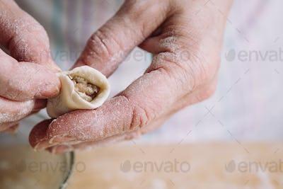 Two hands making meat dumplings.