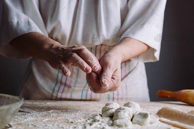 Two hands making dough for meat dumplings.