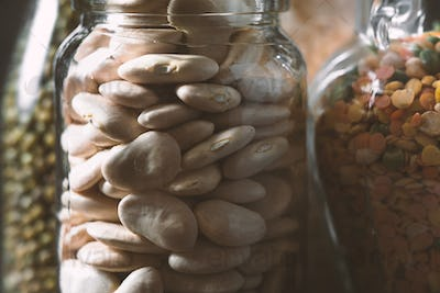 Large white beans in a glass jar is a side view