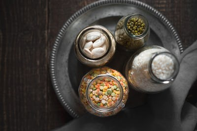 White beans, green beans, lentils and rice in cans on a tin plate