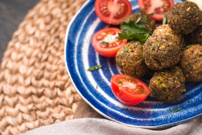 Falafel with tomato and celery on a blue plate on a wicker napkin