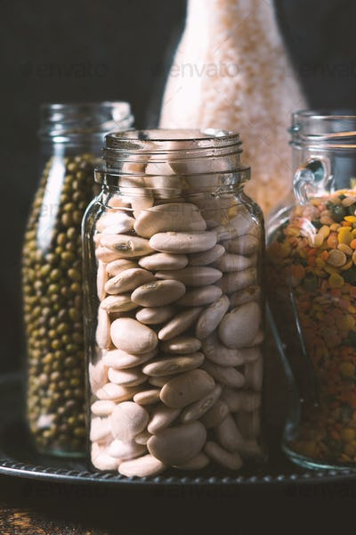 Rice, lentils, white beans in bottles side view
