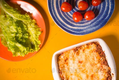 Lasagna, tomatoes, green salad on a yellow background