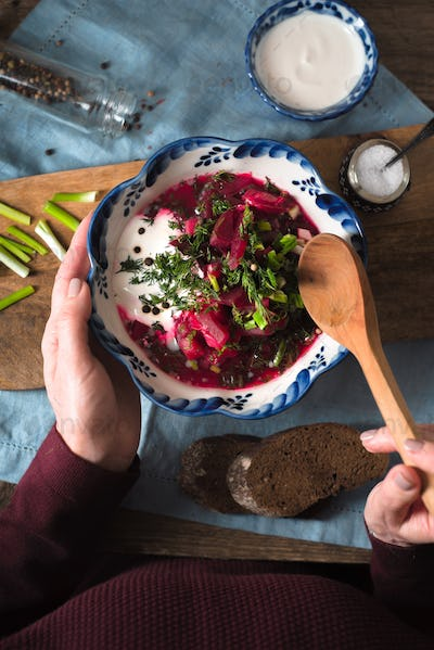 Woman eating traditional beetroot soup borsch top view