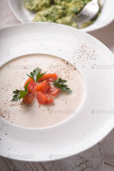 Vichyssoise soup  with salmon in the ceramic plate vertical