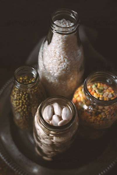 Lentils, white beans, rice in glass bottles side view