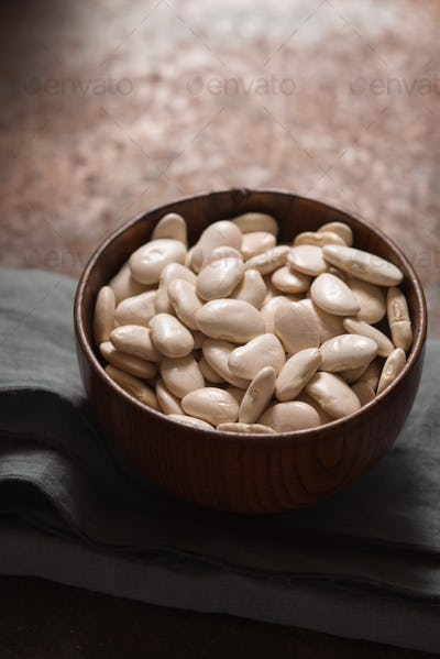 Large white beans in a wooden bowl side view
