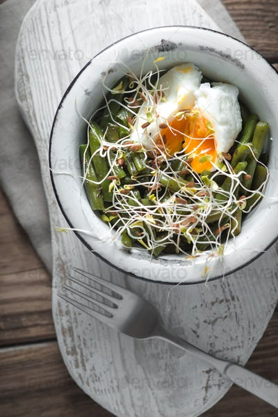 Salad with beans, sprouted flax and quail eggs in a metal bowl and fork