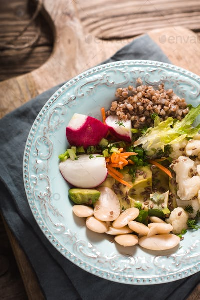 Vegetable salad with buckwheat in turquoise ceramic bowl
