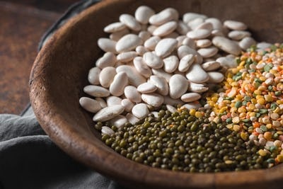 Placer green and white beans in a wooden bowl closeup