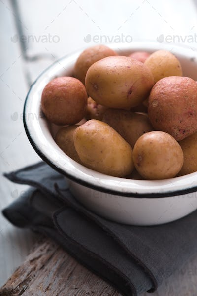 Raw potatoes in a white bowl on a napkin side view